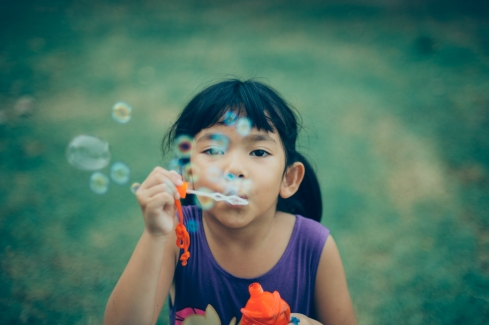 Asian little girl happy with water bubble in vintage color tone